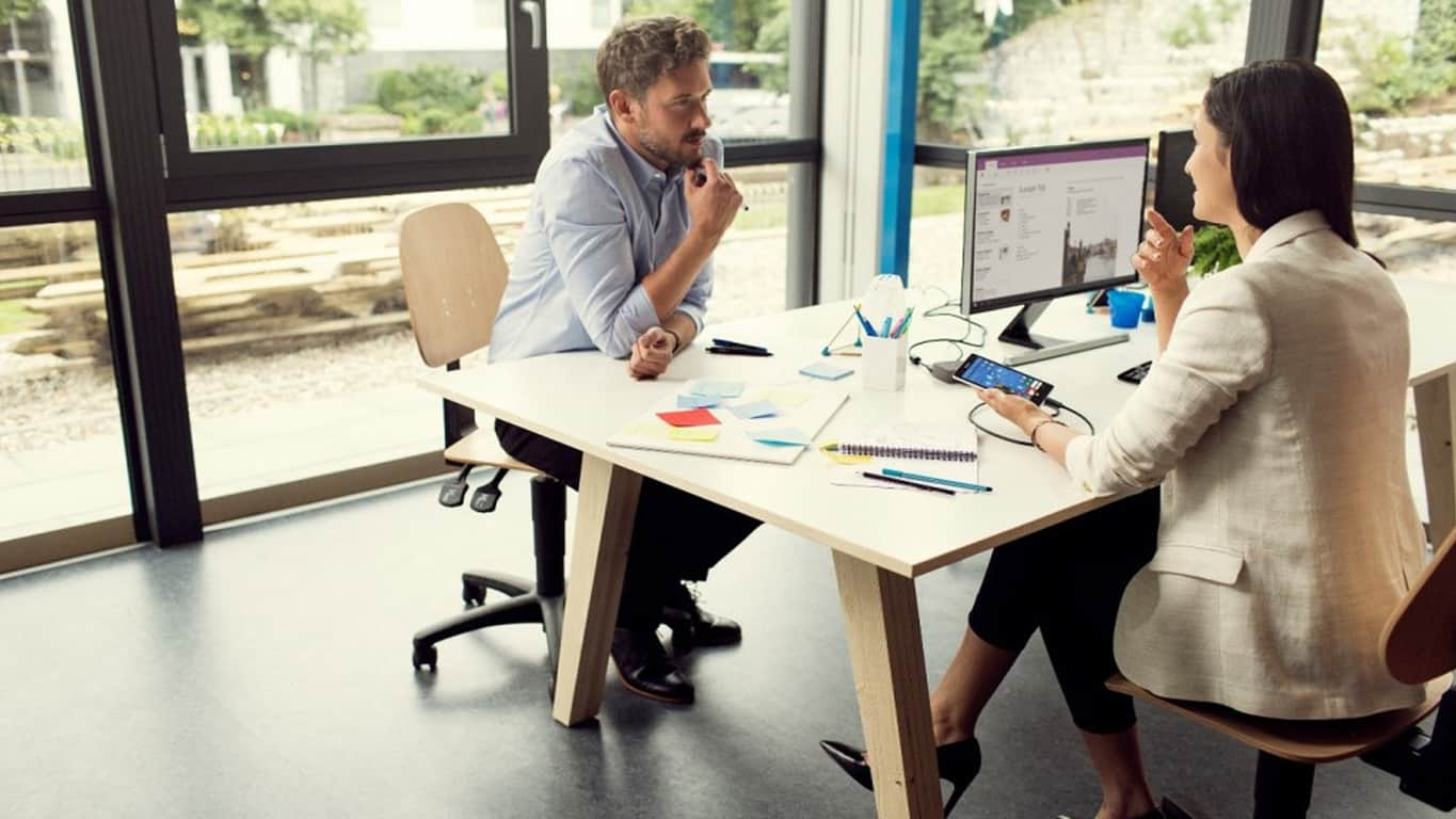 Man and woman in an office using Microsoft Continuum on a Windows Phone and monitor