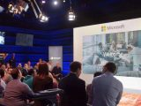 """People looking at a display showing """"welcome"""" text in a microsoft studio"""