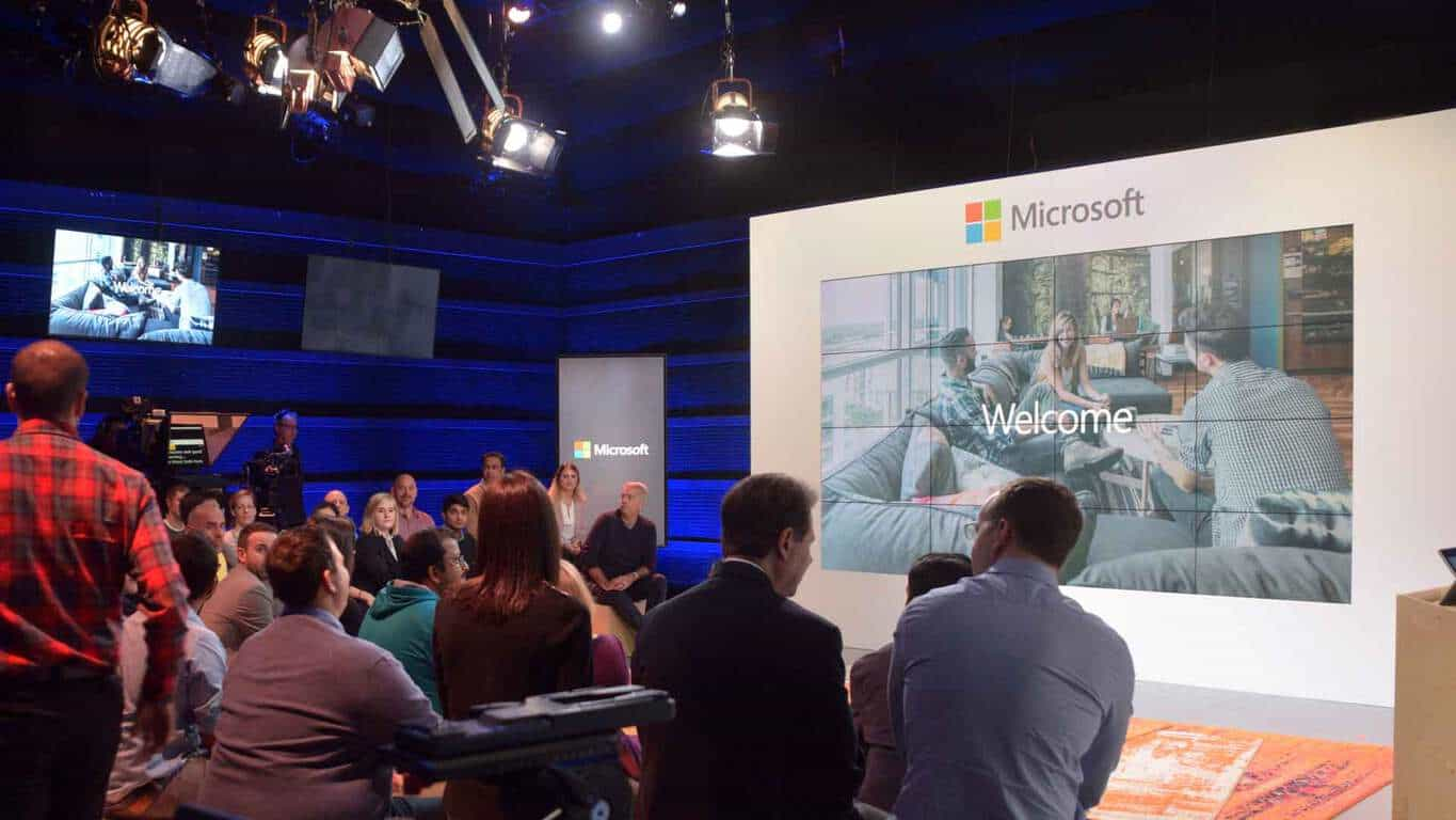 "People looking at a display showing ""Welcome"" text in a Microsoft studio"