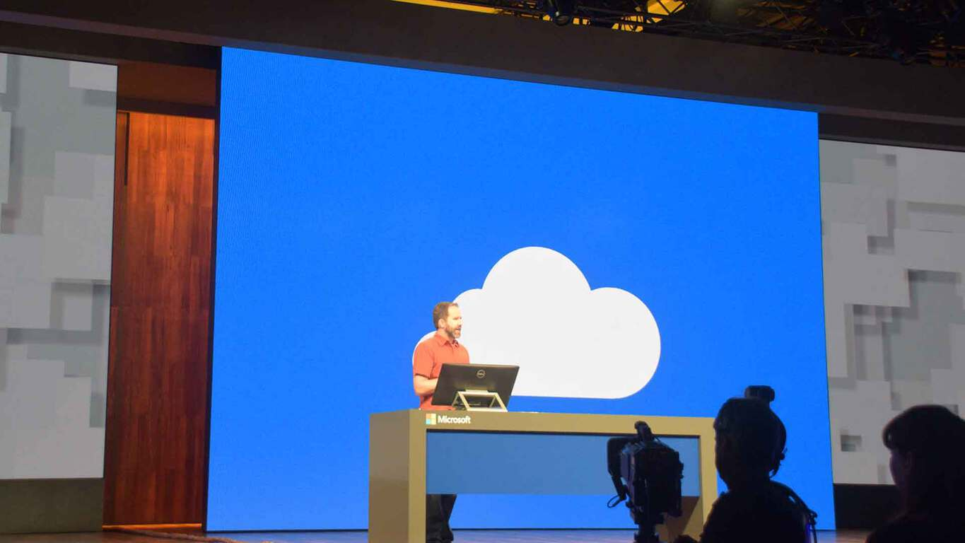 Photo showing a Microsoft employee speaking in front of a large blue screen showing a white cloud OneDrive icon